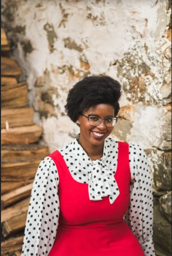 Elizabeth Crowder, a Black woman wearing glasses and a red dress, smiles at the camera.